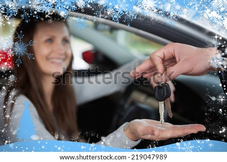 Composite image of happy woman receiving car keys against snow - stock photo