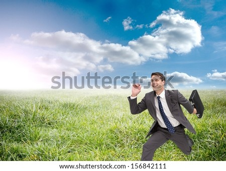 Composite image of joyful businessman holding a suitcase and running in the grass