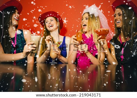 Composite image of Laughing friends at a hen night drinking cocktails against snow falling - stock photo