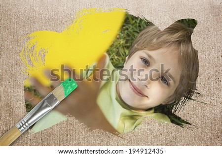 Composite image of little boy smiling at camera with paintbrush dipped in green against weathered surface - stock photo