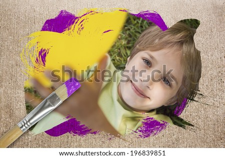 Composite image of little boy smiling at camera with paintbrush dipped in purple paint against weathered surface - stock photo