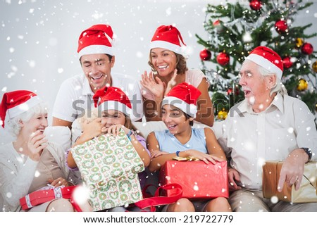 Composite image of Little girl opening christmas present against snow falling - stock photo