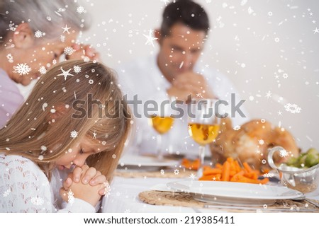 Composite image of Little girl saying grace with family against snow falling - stock photo