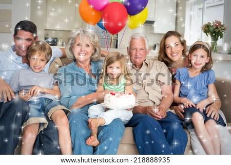 Composite image of Multigeneration family celebrating girls birthday against snow - stock photo