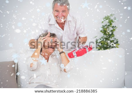 Composite image of Old man hiding eyes of his wife for a gift against snow - stock photo
