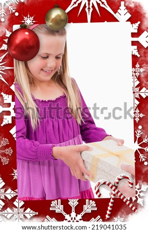 Composite image of Portrait of a girl receiving a present with christmas themed page - stock photo