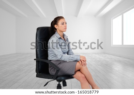 Composite image of portrait of a serious businesswoman sitting on an armchair - stock photo