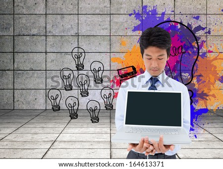 Composite image of portrait of a young businessman showing a laptop - stock photo