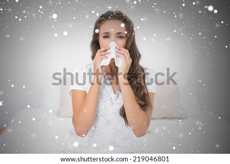 Composite image of pretty brunette blowing her nose against snow - stock photo