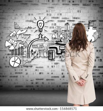 Composite image of rear view of businesswoman crossing hands behind back looking at economic illustrations on grey wall - stock photo
