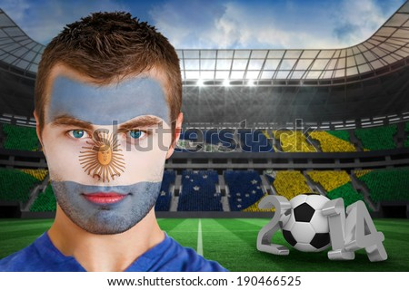 Composite image of serious young argentina fan with face paint against large football stadium with brasilian fans - stock photo