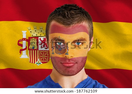 Composite image of serious young spain fan with facepaint against digitally generated spanish national flag