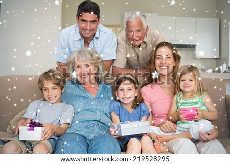 Composite image of Siblings holding gifts with family in living room against snow - stock photo