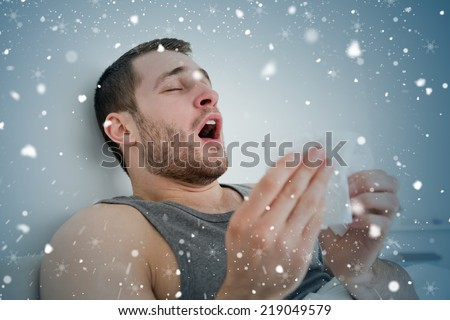 Composite image of sick man sneezing against snow falling - stock photo