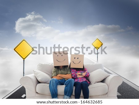 Composite image of silly employees with arms folded wearing boxes on their heads with smiley faces on a couch - stock photo