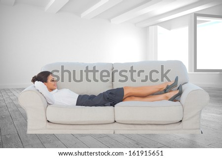 Composite image of smiling business woman lying down on the couch in the office - stock photo