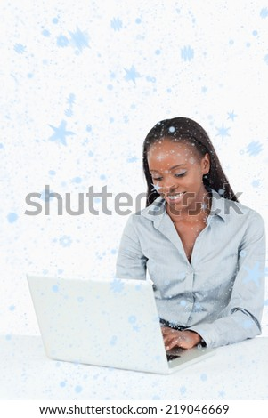 Composite image of Smiling businesswoman using a laptop with snow falling
