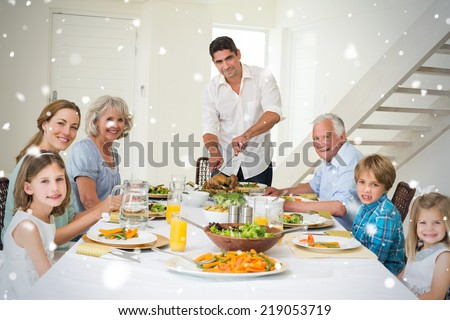 Composite image of Smiling father serving meal to family against snow falling