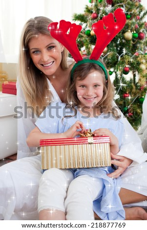 Composite image of Smiling mother and her daughter unpacking Christmas gifts with night sky - stock photo