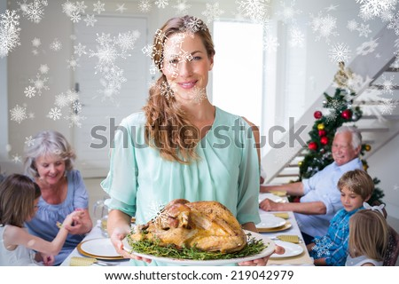 Composite image of Smiling mother with Christmas meal against snowflakes - stock photo