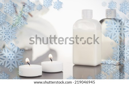 Composite image of snowflake frame against white orchid glass flasks and lighted white candles