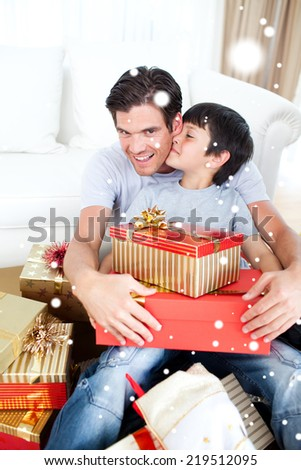 Composite image of Son kissing his father after receiving a Christmas gift with snow falling
