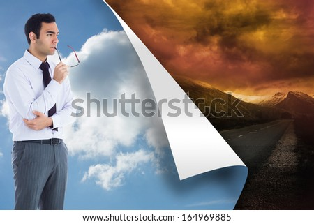 Composite image of unsmiling businessman holding glasses