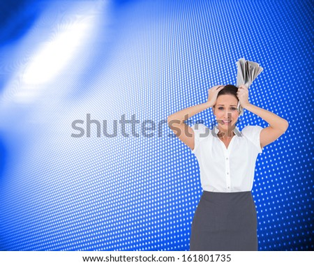 Composite image of worried stylish businesswoman holding newspaper - stock photo