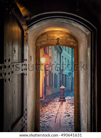 Composite image with nocturnal view from ancient door on medieval street by winter time, European old town