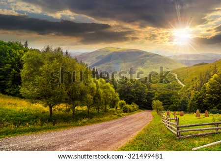 composite landscape. fence near road going down the hill through meadow and forest to the high mountains in evening light - stock photo