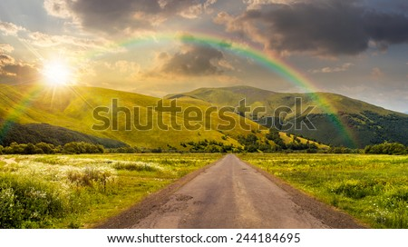 composite landscape with abandoned asphalt road rolls through meadows with flowers going to high  mountains in sunset light with rainbow - stock photo