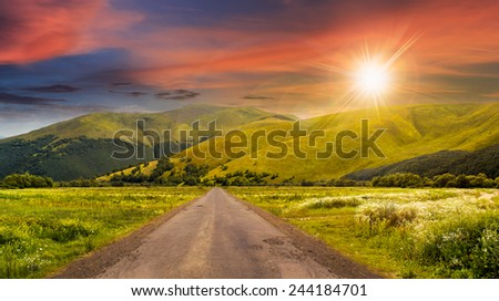 composite landscape with abandoned asphalt road rolls through meadows with flowers going to high  mountains in sunset light - stock photo