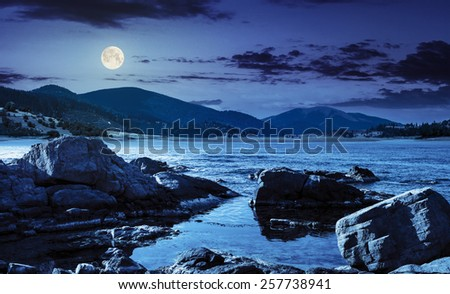 composite landscape with rocky lake shore and some boulders in mountains at night in full moon light - stock photo