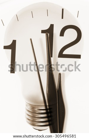 Composite of Clock Hands and Light Bulb - stock photo