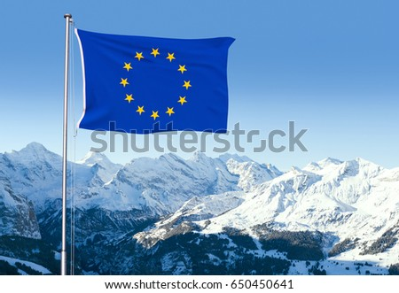 Composite with the flag of the European Union fluttering in the wind and snow capped mountains in the background.