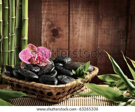 composition bamboo grove, pink orchid and black zen stones in the bowl on the wooden background - stock photo