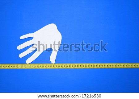 Composition from a silhouette of a hand and a measuring tape. - stock photo