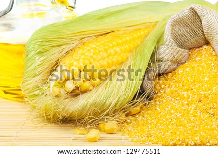 Composition from corn, maize flour and corn oil on the mat isolated on white background - stock photo