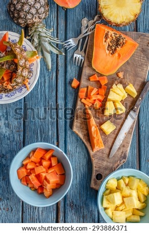 Composition from healthy natural slices fruit of papaya and pineapple slices in blue bowl over on a rustic blue chalkboard. Colorful rustic image from above  - stock photo