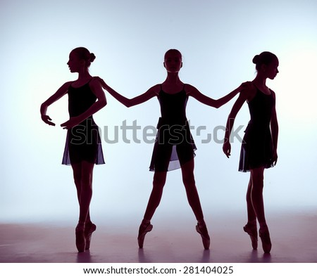 Composition from silhouettes of three young dancers in ballet poses on a gray background.  The outline shooting - silhouettes of girls. - stock photo