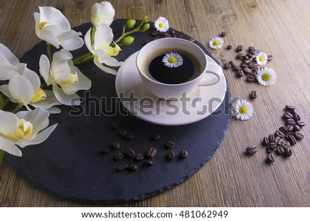 Composition made from cup of black tea with a black and brown background. Cup of black coffee with white flower, chamomile and coffee beans. It simbolizes nice morning with tasty tea.