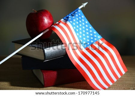 Composition of  American flag, books and apple  on wooden table, on dark background - stock photo