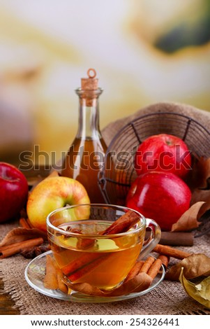 Composition of  apple cider with cinnamon sticks, fresh apples and autumn leaves on wooden background - stock photo