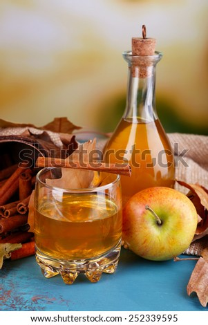 Composition of apple cider with cinnamon sticks, fresh apples and autumn leaves on wooden table, on bright background - stock photo