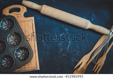 Composition of baking and kitchen accessories on black table. Wooden and metal dishes tableware, cookware, kitchenware. Different support stuff. Baking preparation concept. Top view. Copy space. - stock photo