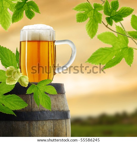Composition of beer in glass with barrel and hop plant - stock photo