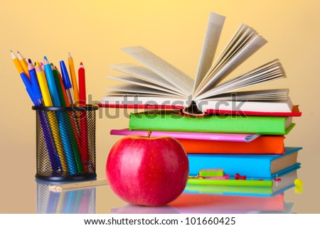 Composition of books, stationery and an apple on bright colorful background - stock photo