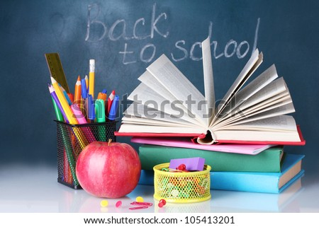 Composition of books, stationery and an apple on the teacher's desk in the background of the blackboard. Back to school. - stock photo