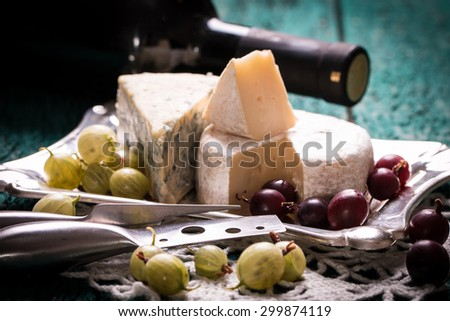 Composition of cheese, berries, bottles and glasses of wine on a wooden table ,anniversary romantic dinner.