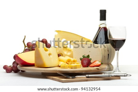 Composition of cheese, grapes, bottles and glasses of wine and strawberries on a wooden round tray on a white tablecloth, isolated on a white background - stock photo